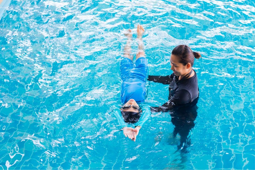 girl-learning-to-swim-with-coach-at-the-leisure-center-picture-id935932824