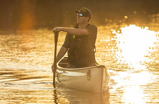 Officer paddling in a canoe at sunset